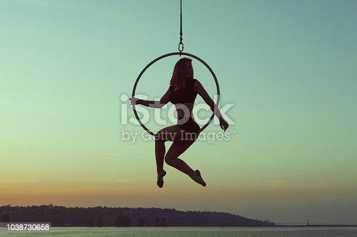 istock Girl gymnast sits on an acrobatic ring. 1038730658