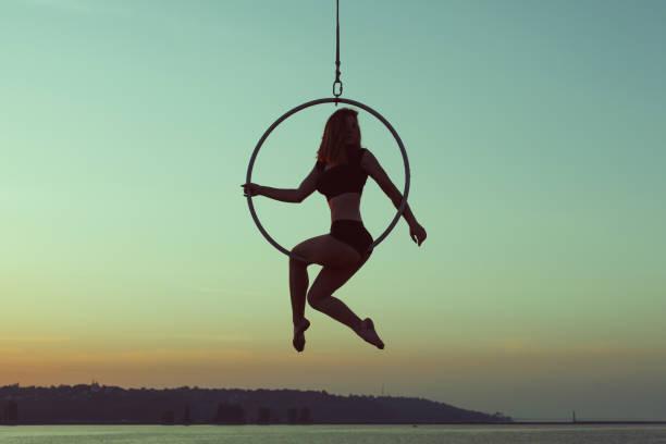 turnerin mädchen sitzt auf einem akrobatischen ring. - hula hoop workout stock-fotos und bilder