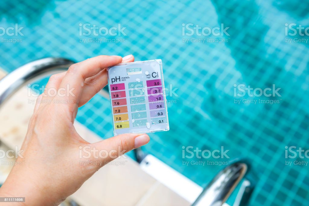 Girl hand holding mini water testing test kit over blurred swimming pool background stock photo