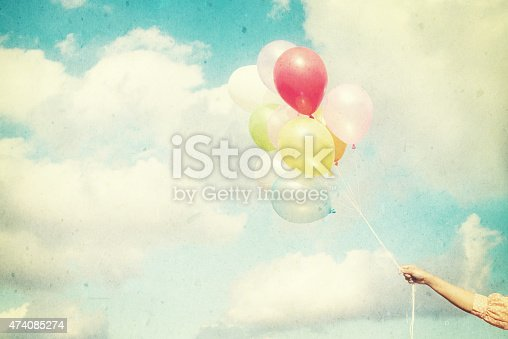istock Girl hand holding multicolored balloons 474085274