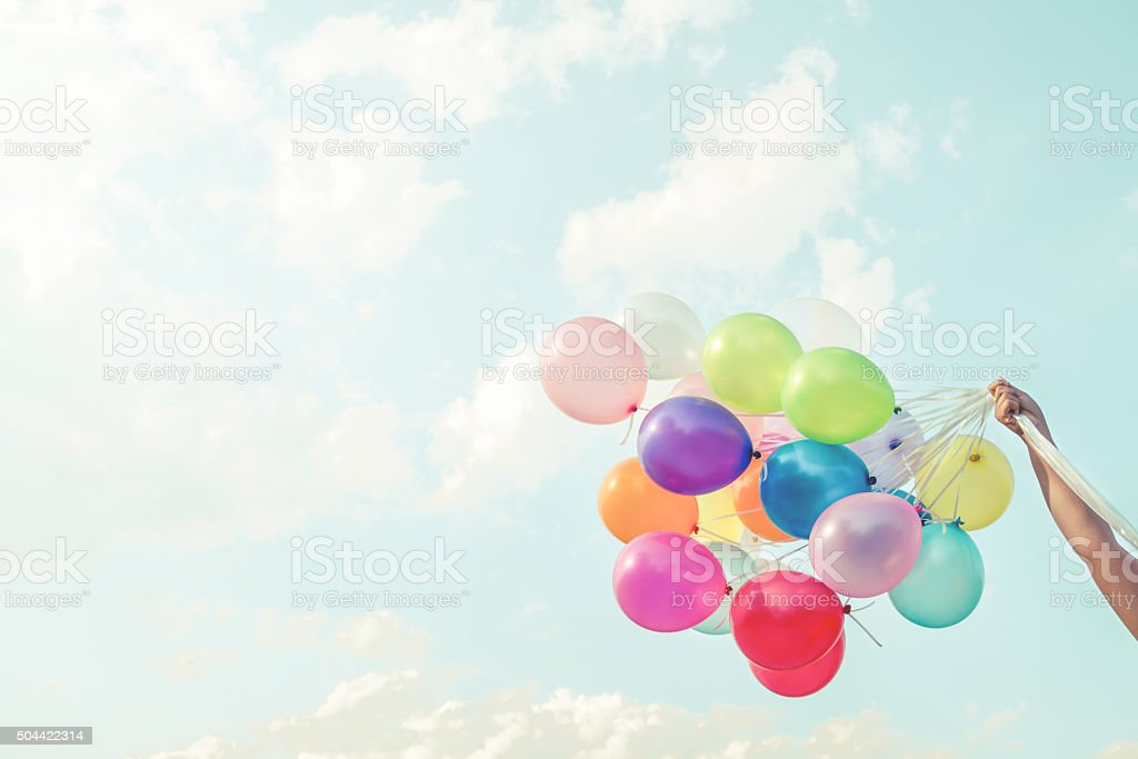 Girl hand holding multicoloured balloons stock photo
