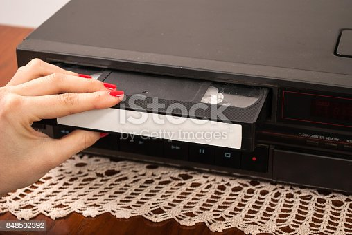 istock Girl hand inserting blank VHS cassette in old video recorder 848502392