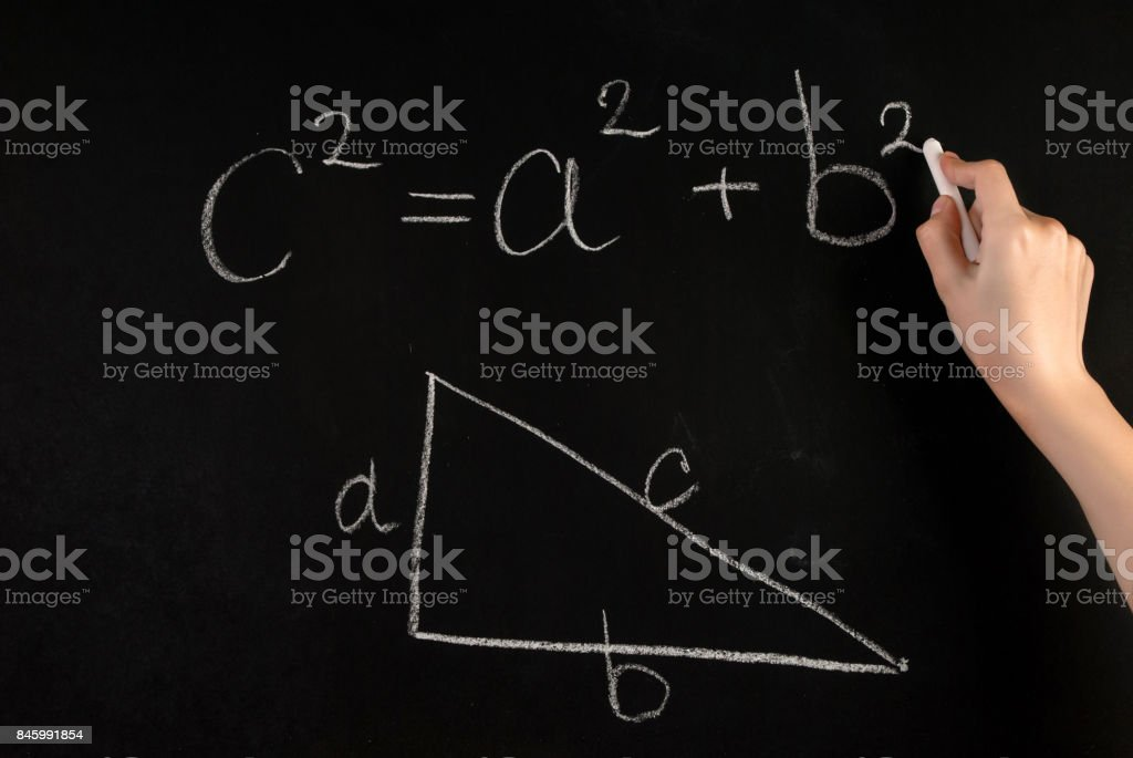 Girl hand write Pythagoras Theorem and angled triangle with on school blackboard with white chalk stock photo