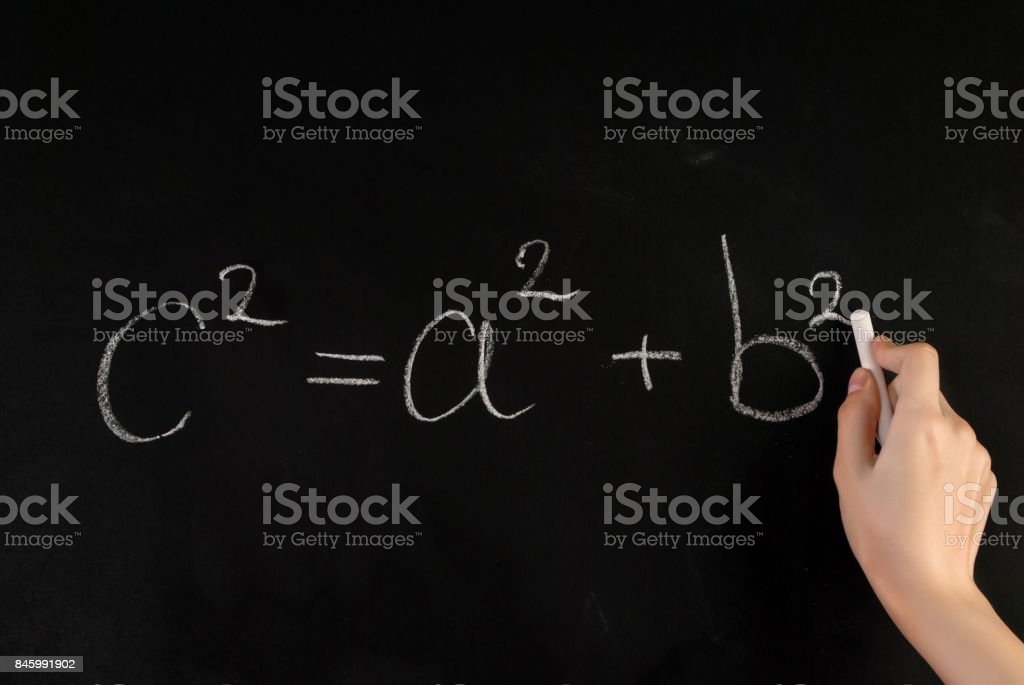 Girl hand write Pythagoras Theorem on school blackboard with white chalk stock photo