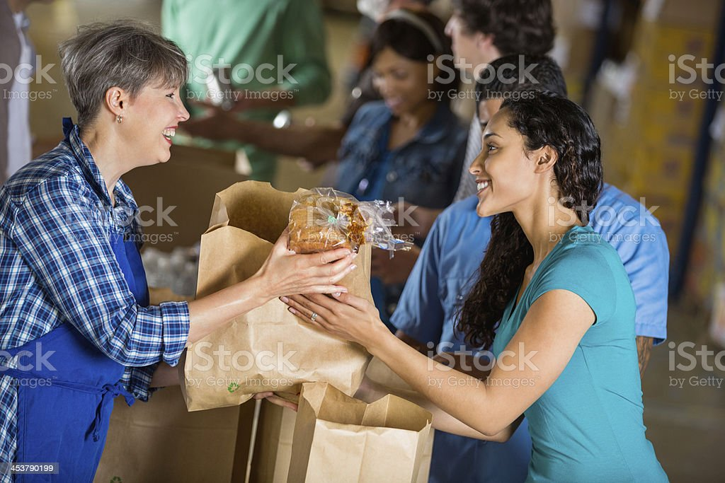 Girl handing a bag of food to a woman in an apron royalty-free stock photo