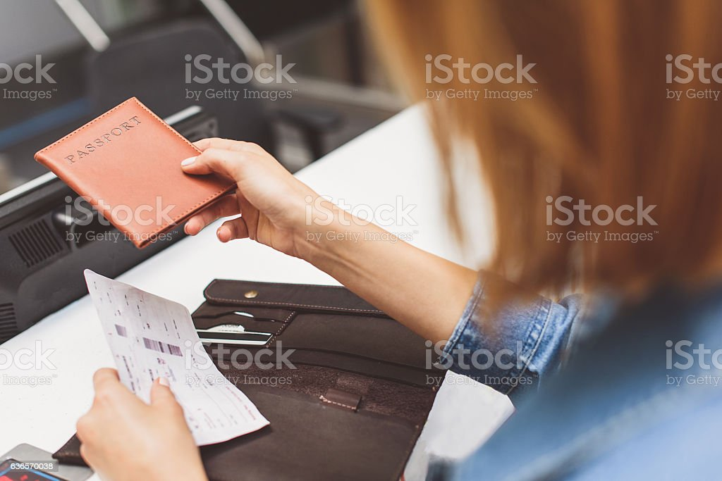 Girl handing over boarding pass to attendant stock photo