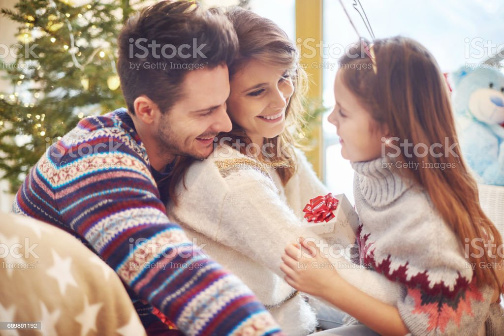 Girl handing over little gift to parents stock photo