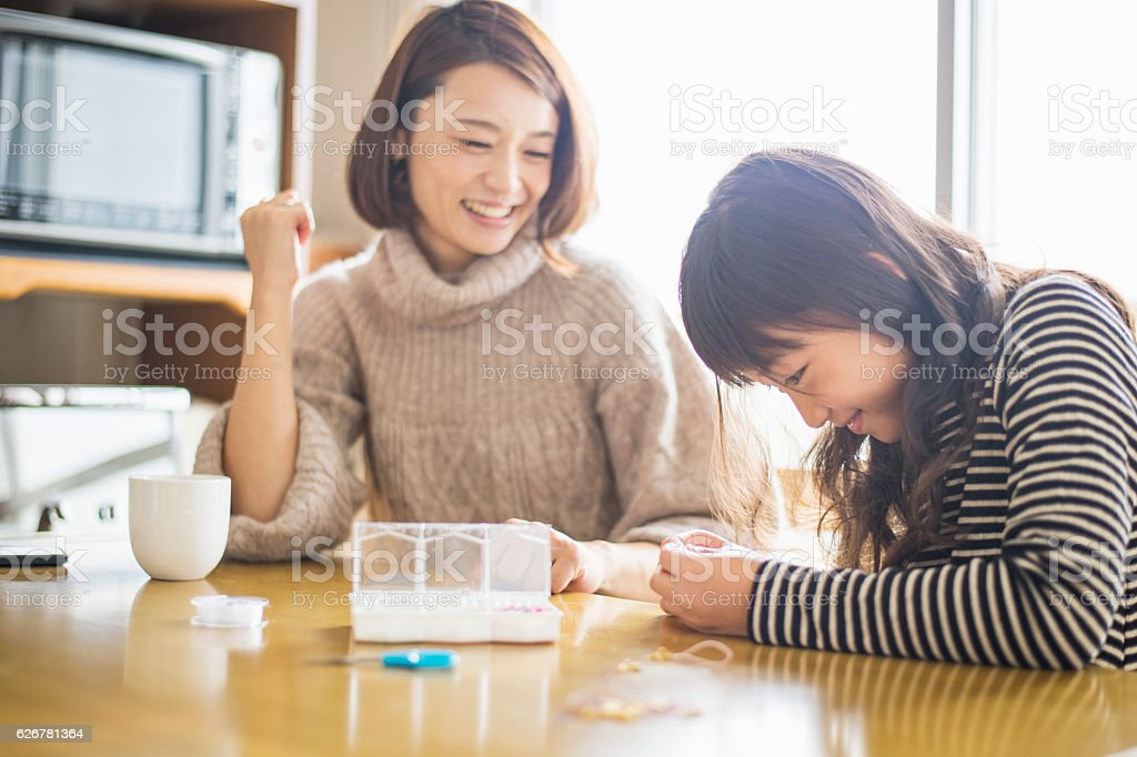 Girl handmade beads accessories with mother stock photo