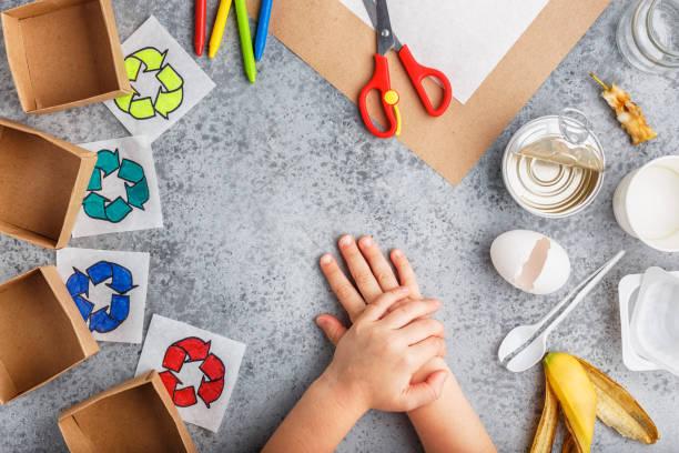 mädchen hände machen recycling-spiel in papier auf grauem hintergrund bunt - eco bastelarbeiten stock-fotos und bilder