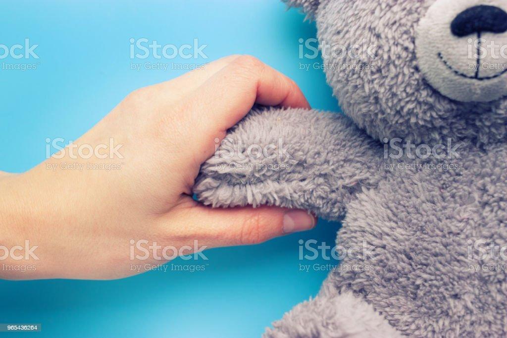 手持泰迪熊的女孩手 - 免版稅一個人圖庫照片