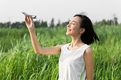 girl standing outdoors ,reeds, holding a model airplane, a symbol of the dream, wish