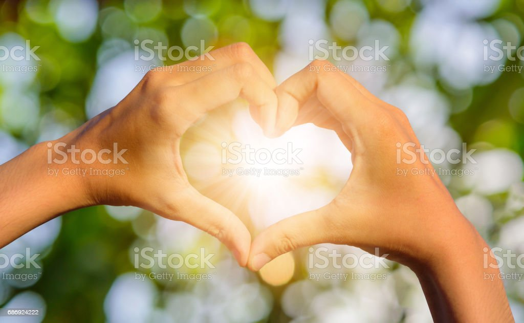 Girl hands in shape of love heart on blurred natural bokeh background – Foto