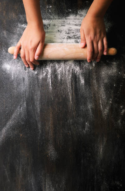 Girl hands keep rolling pin with flour on dark black table, baking background, top view, copy space for your text, meru, recipe. Banner Girl hands keep rolling pin with flour on dark black table, baking background, top view, copy space for your text, meru, recipe. Banner kneading dough stock pictures, royalty-free photos & images