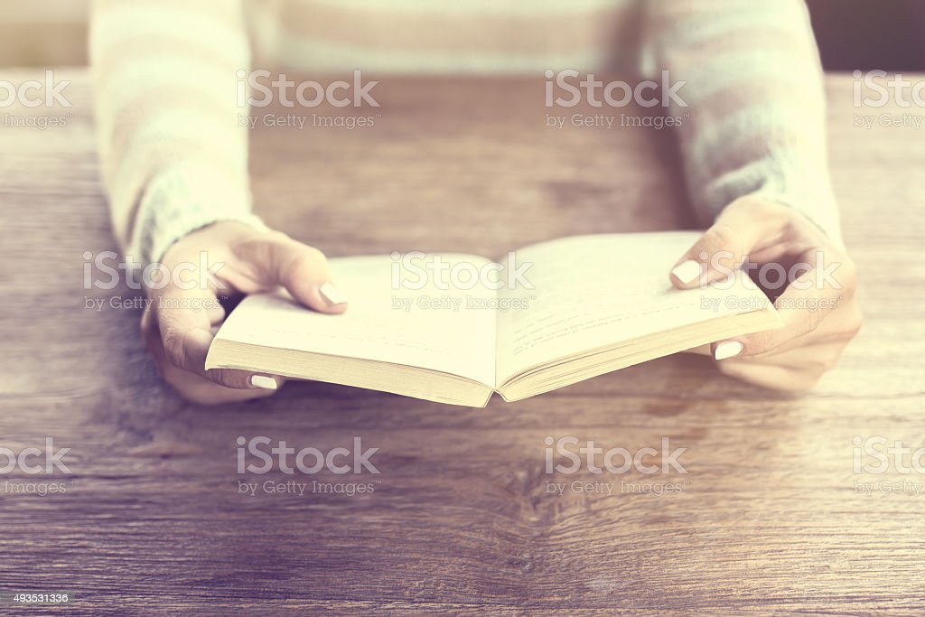 Girl hands keeping an open book on a wooden table stock photo