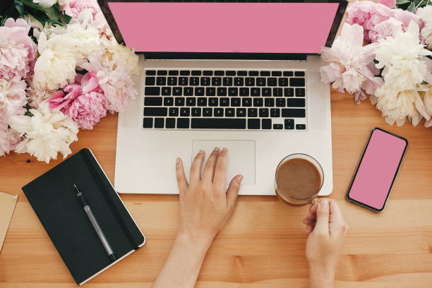 girl hands on stylish laptop with empty screen and coffee, phone, black notebook and peonies on rustic wooden table. freelance concept flat lay. workplace. space for text.  women's day - femininity stock pictures, royalty-free photos & images