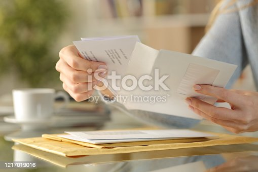 istock Girl hands opening an envelope on a desk at home 1217019016