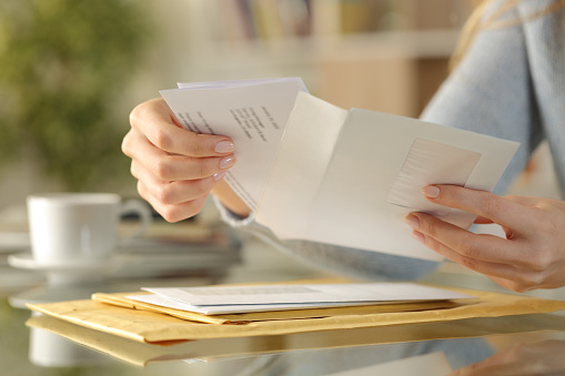 Close up of girl hands opening an envelope with a letter inside on a desk at home