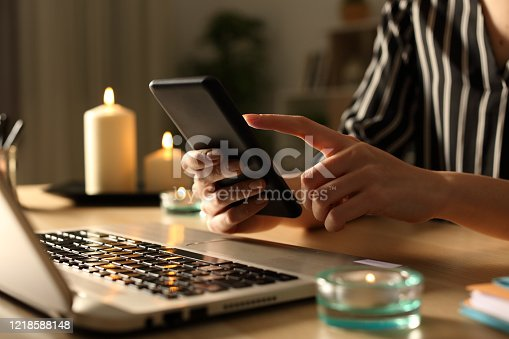 693910734 istock photo Girl hands using phone on power outage with candles 1218588148