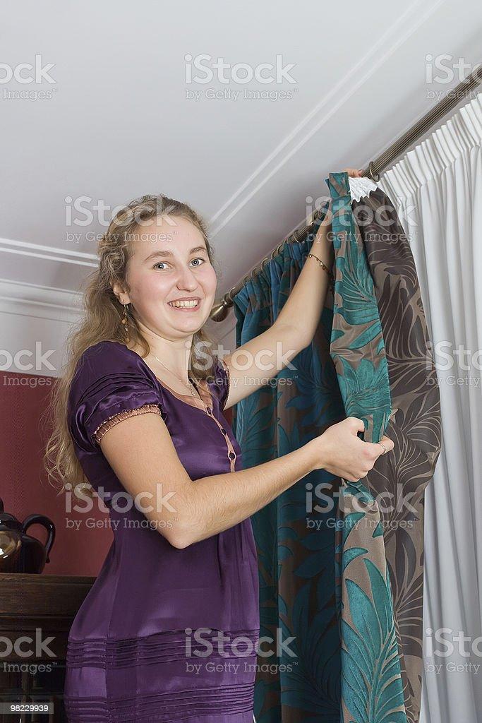 Girl hang up a curtain royalty-free stock photo