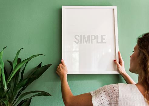 Meisje Opknoping Van Een Frame Op Een Groene Muur Stockfoto en meer beelden van Afbeelding