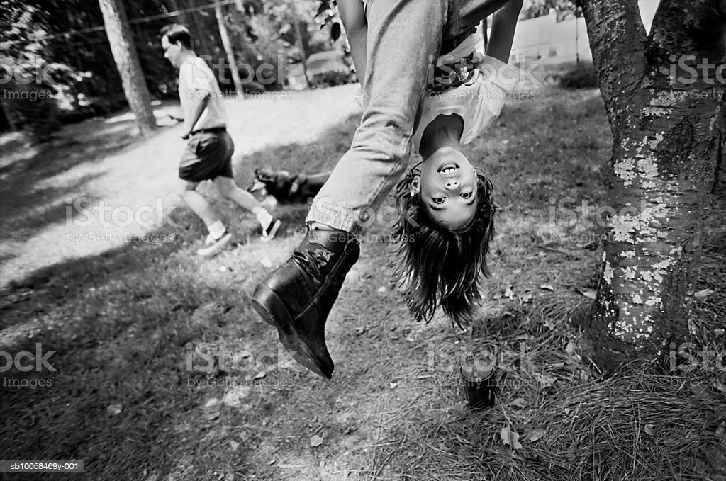 Girl (10-11) hanging upside down from tree (B&W) photo libre de droits