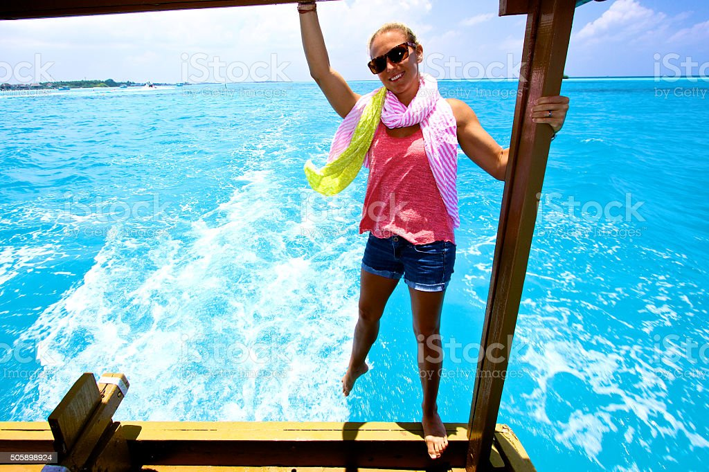 Girl hangs off the back of boat in the tropics stock photo