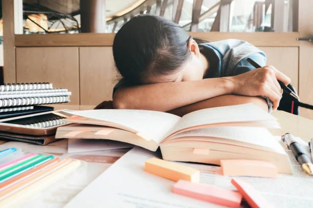 Girl hart lesen und schlafen in der Bibliothek. – Foto