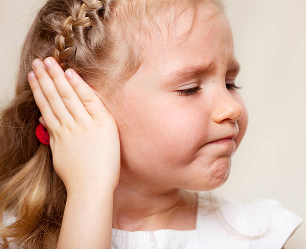 Girl has a sore ear Child has a sore ear. Little girl suffering from otitis human ear stock pictures, royalty-free photos & images
