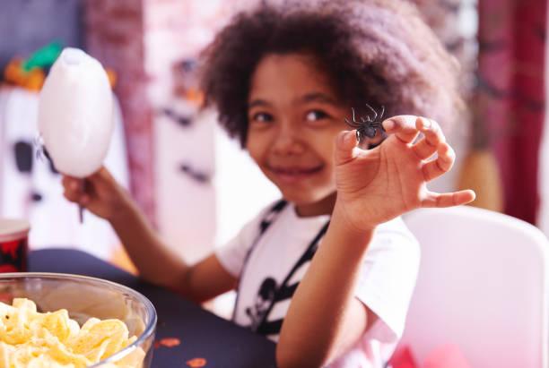 mädchen mit einem snack während der halloween-party - piratenparty snacks stock-fotos und bilder