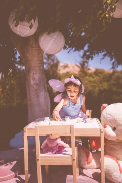 mädchen mit einer tee-party mit ihrem spielzeug im garten - sommerfest kindergarten stock-fotos und bilder