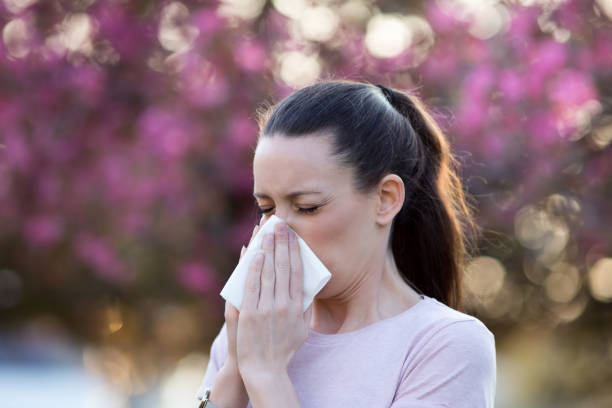 Girl having allergy symptoms in spring Young pretty woman blowing nose in front of blooming tree. Spring allergy concept antihistamine stock pictures, royalty-free photos & images