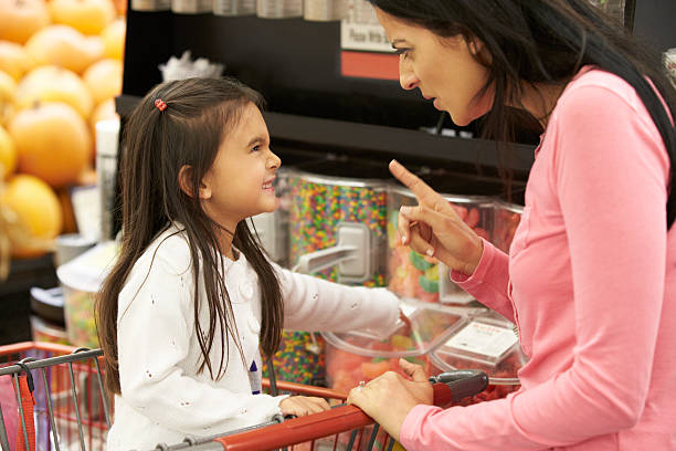 Girl Having Argument With Mother At Candy Counter Girl Having Argument With Mother At Candy Counter In Supermarket scolding stock pictures, royalty-free photos & images