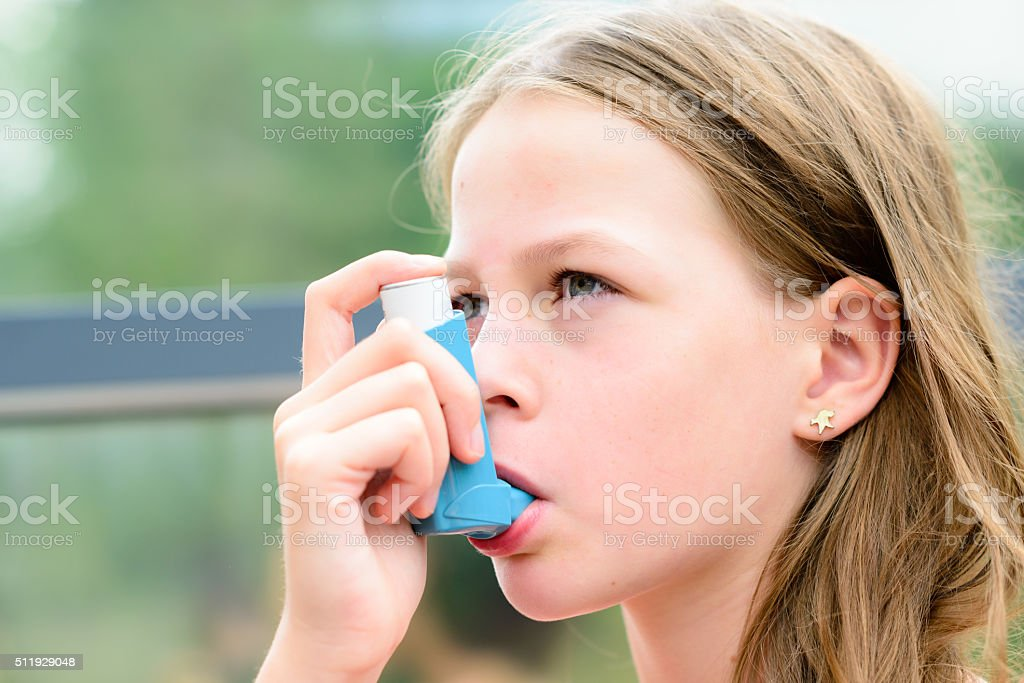 Girl having asthma using the asthma inhaler stock photo