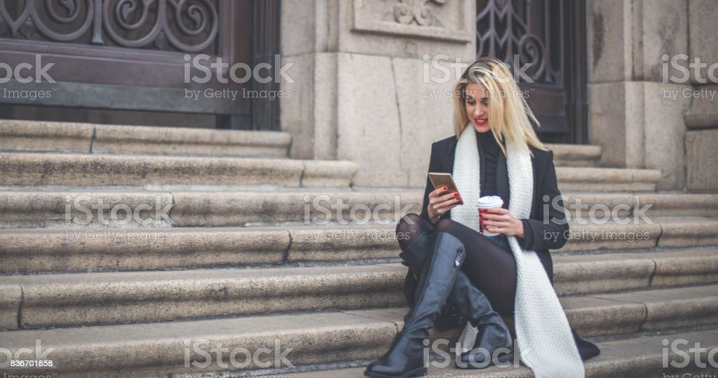 Girl having coffee on steps stock photo