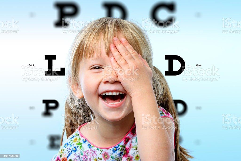 Girl having fun at vision test. stock photo