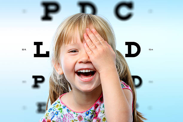 girl having fun at vision test. - optical instrument stock pictures, royalty-free photos & images