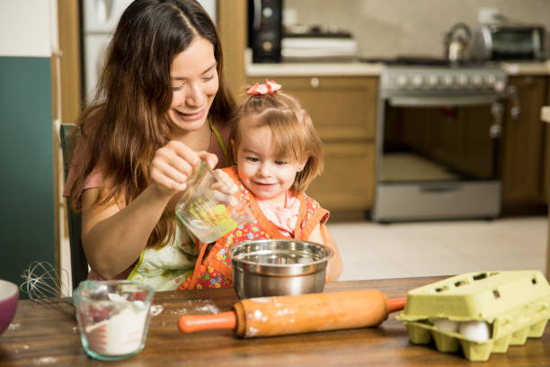 Girl having fun cooking with her mother stock photo