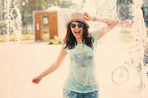 fille s'amusant dans une fontaine - fontaine photos et images de collection