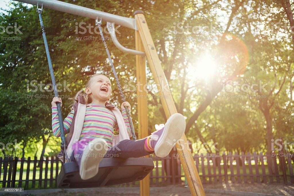 Girl having fun on swing stock photo