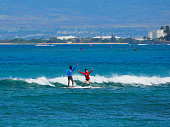 USA, Hawaii - August 31, 2018: Asian tourist woman learning to surf in Waikiki, Honolulu, Oahu.