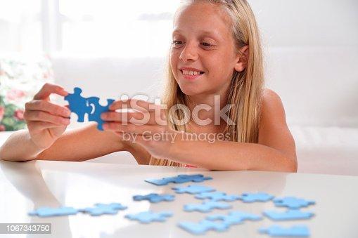 175496485 istock photo Girl having fun with jigsaw puzzle 1067343750
