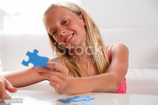 175496485 istock photo Girl having fun with jigsaw puzzle 1069104758