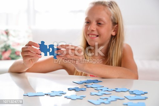 175496485 istock photo Girl having fun with jigsaw puzzle 1071324778
