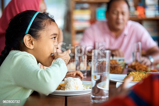 Side view of girl having rice at home. Female child is with grandparents during lunch time. She is sitting with family at table.