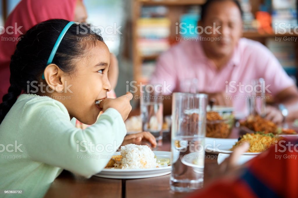 Girl having rice with family at home stock photo