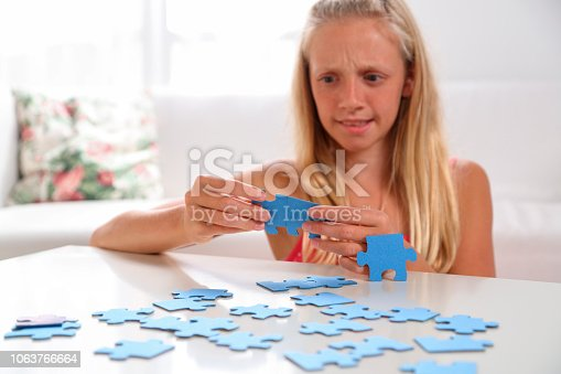 istock Girl having trouble with jigsaw puzzle 1063766664