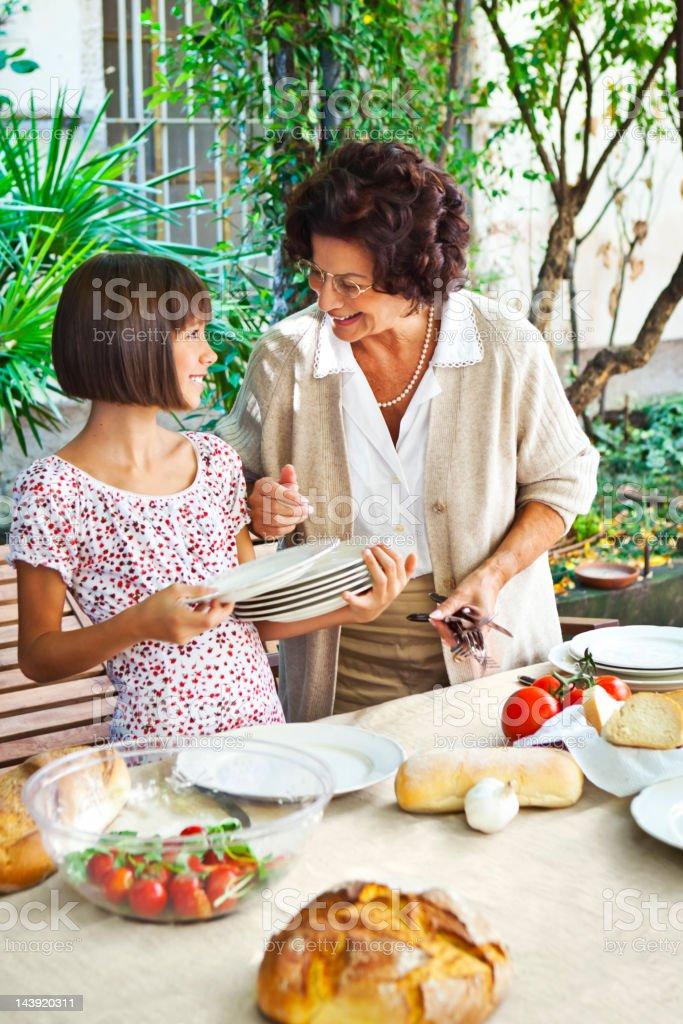 Girl helping grandmother setting table stock photo
