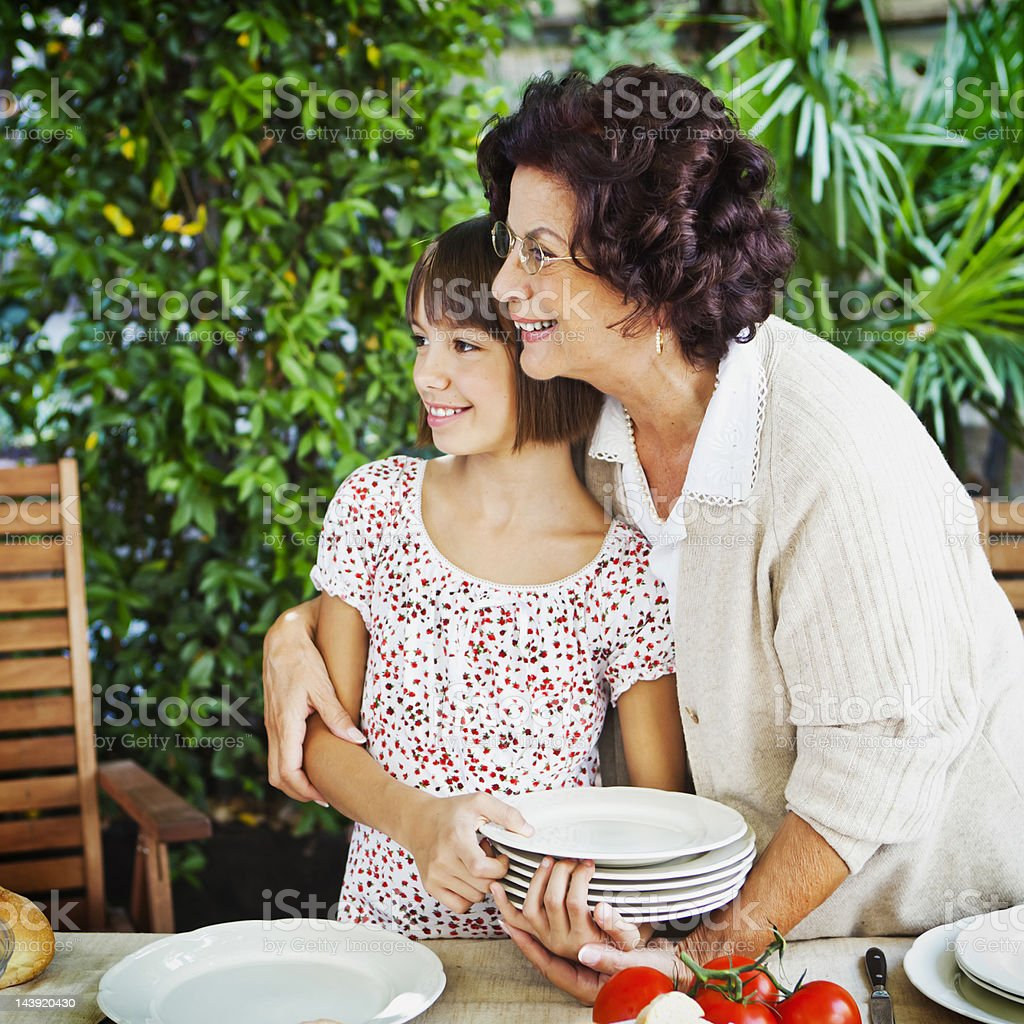 Girl helping grandmother to set table royalty-free stock photo