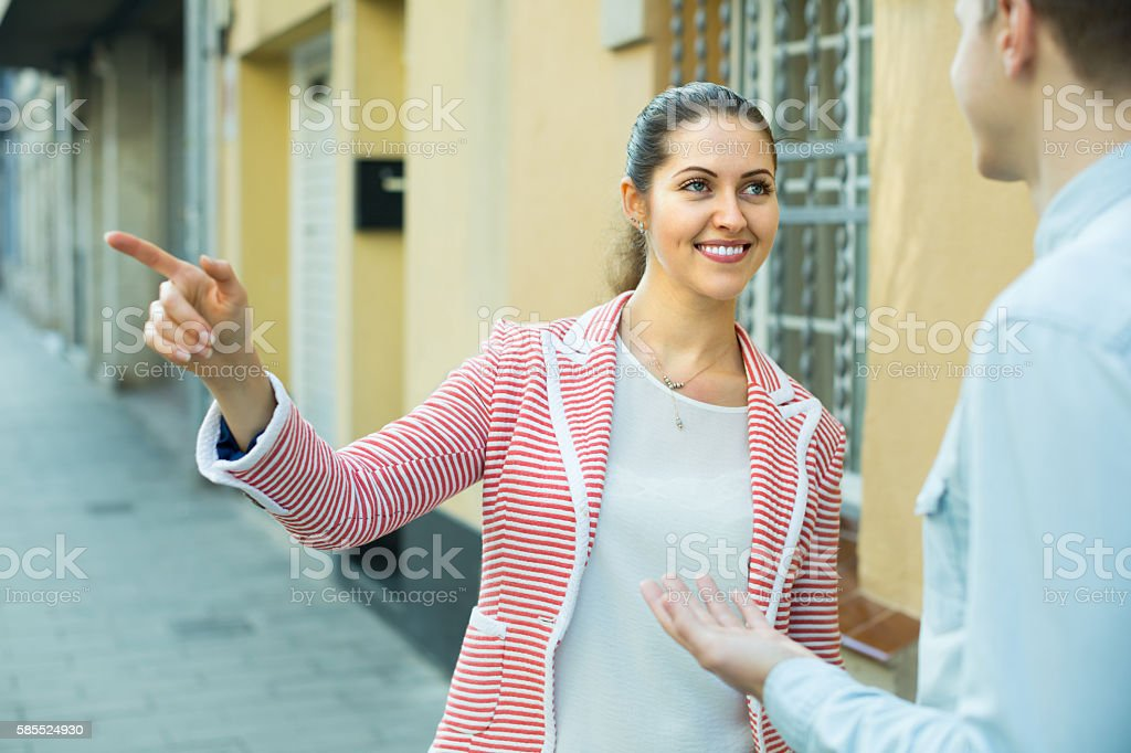 Girl helping lost male tourist stock photo