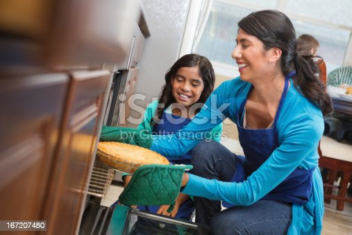 istock Girl helping mom take pie from oven in family kitchen 167207480